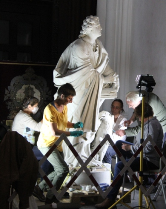 Workers restore  a statue in the cathedral.