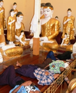 Temple workers take a siesta break under the watchful eyes of Buddhas.