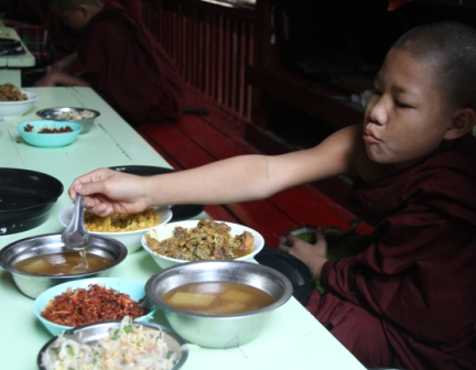 Young monk digs into the many different dishes common to a Myanmar meal.