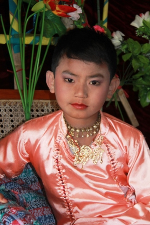 Young boy dressed up and made up for the ceremony before he goes off to become a monk.