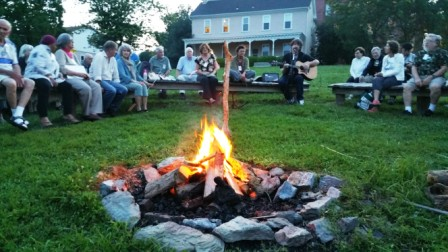 Campfire at the reunion featuring a guitar player and Somemores